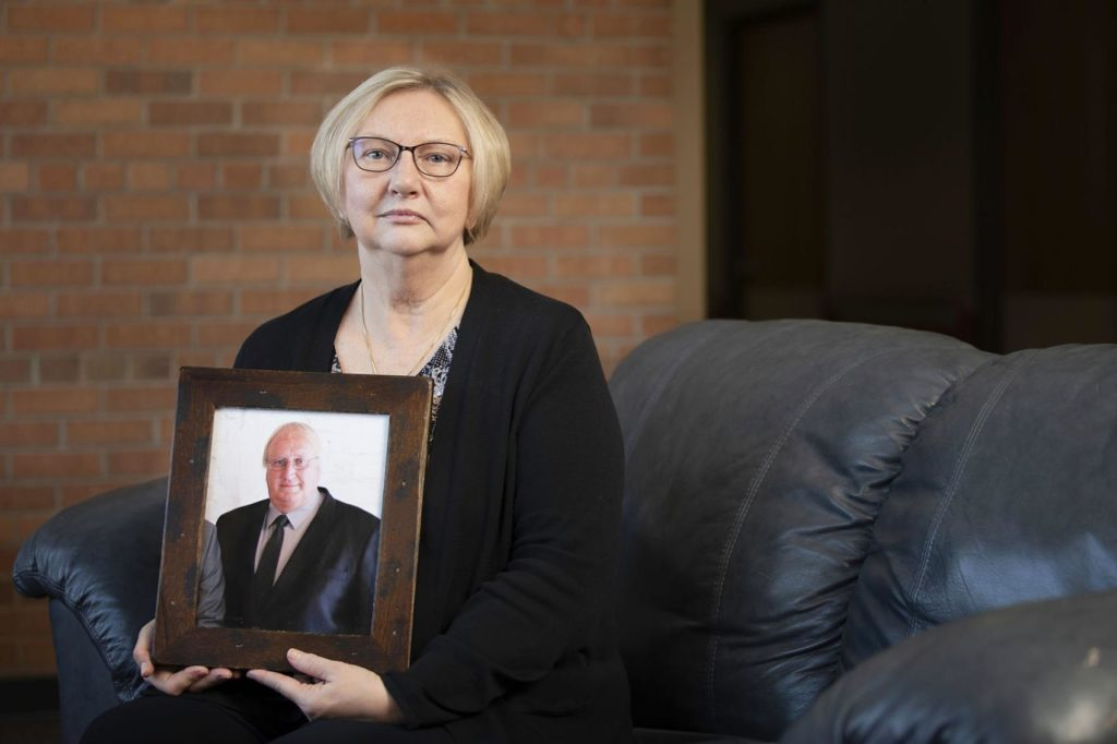 Nancy Buchholz holds her husband Jeff's picture, who died six weeks after being diagnosed with cancer this spring. Nancy got Bind coverage through her employer, Dove Healthcare and the only bill she had to pay for his hospital stay was the $1,900 copayment laid out in the new insurance plan.  the associated press